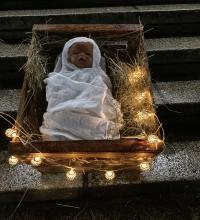 Das Christkind liegt in der kleinen Holzkiste, vor der Grünewald-Schule bei der Heiligabend-Feier unserer PG mit Eva Meder-Thünemann.